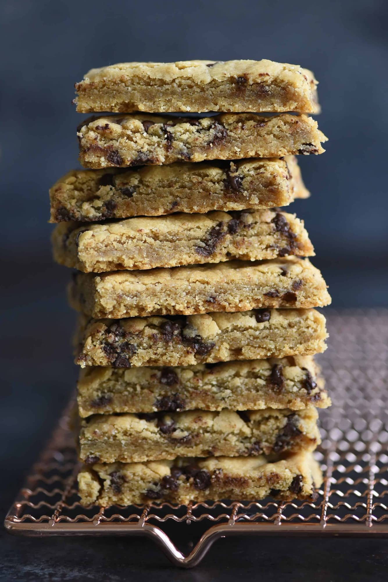 Side view of stack of chocolate chip cookie bars on a cooling rack