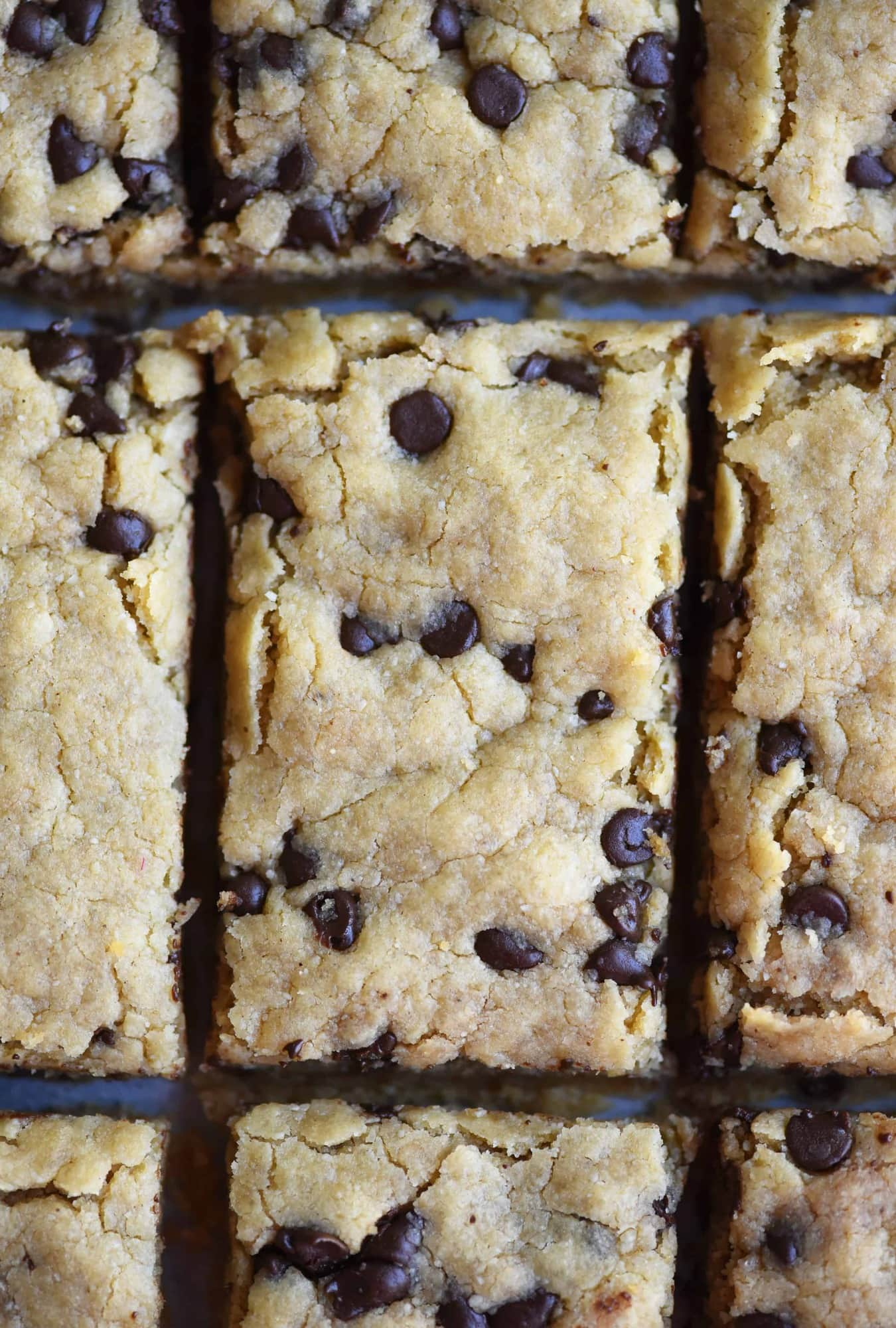 Overhead of chocolate chip cookie bar with bite taken out on a dark background