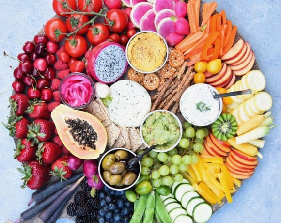 Circular platter filled with rainbow fruits and vegetables, dips and crackers