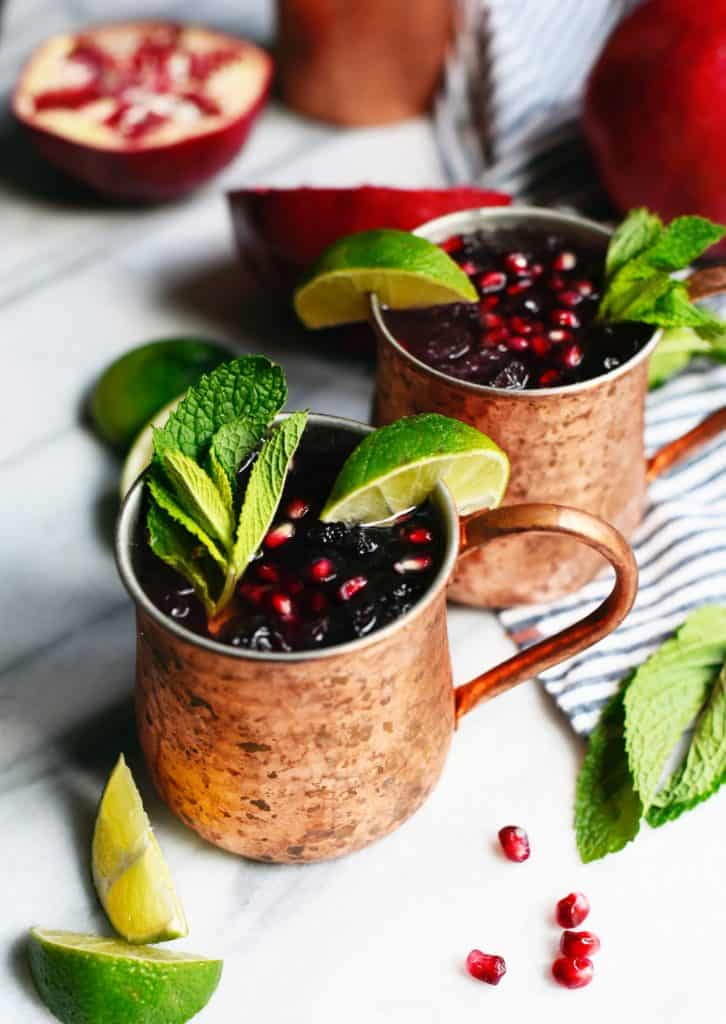 Side view of pomegranate moscow mule garnished with mint and lime