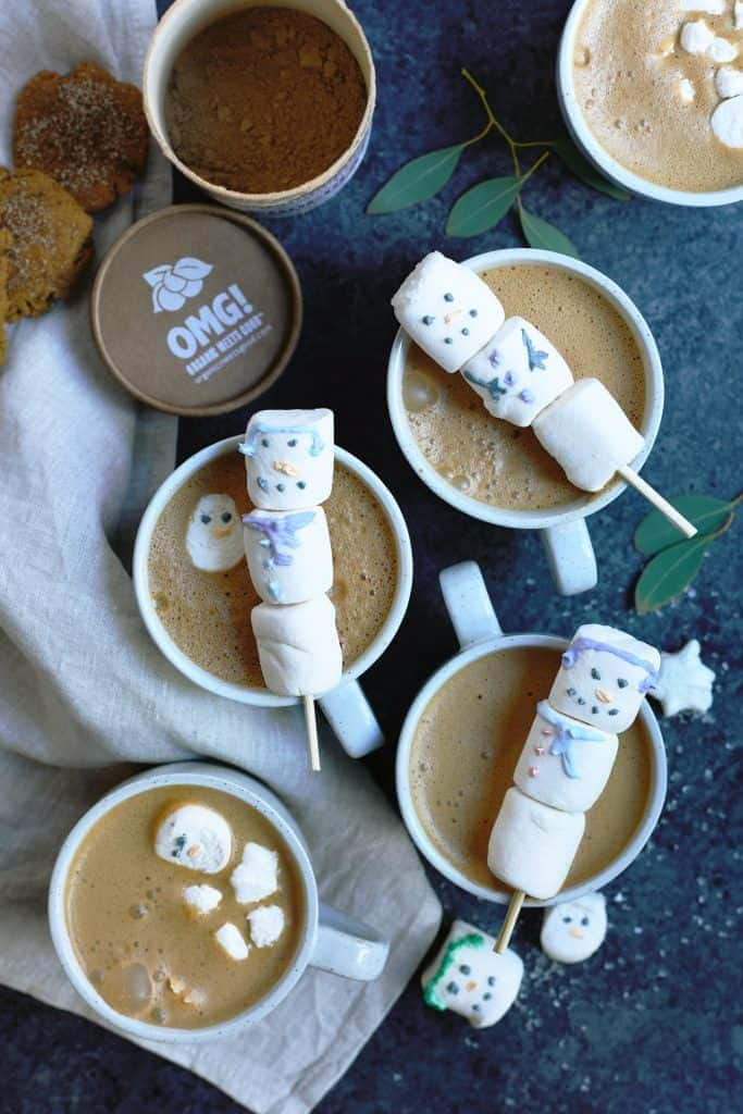 Overhead of mugs of hot cocoa topped with marshmallow snowmen