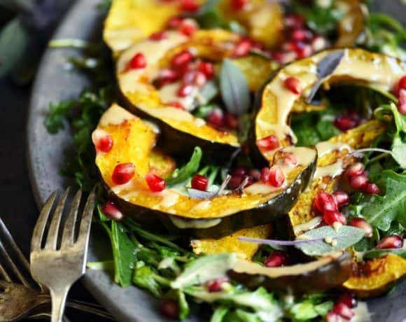 Side view of squash salad with pomegranate and tahini dressing on a silver antique platter