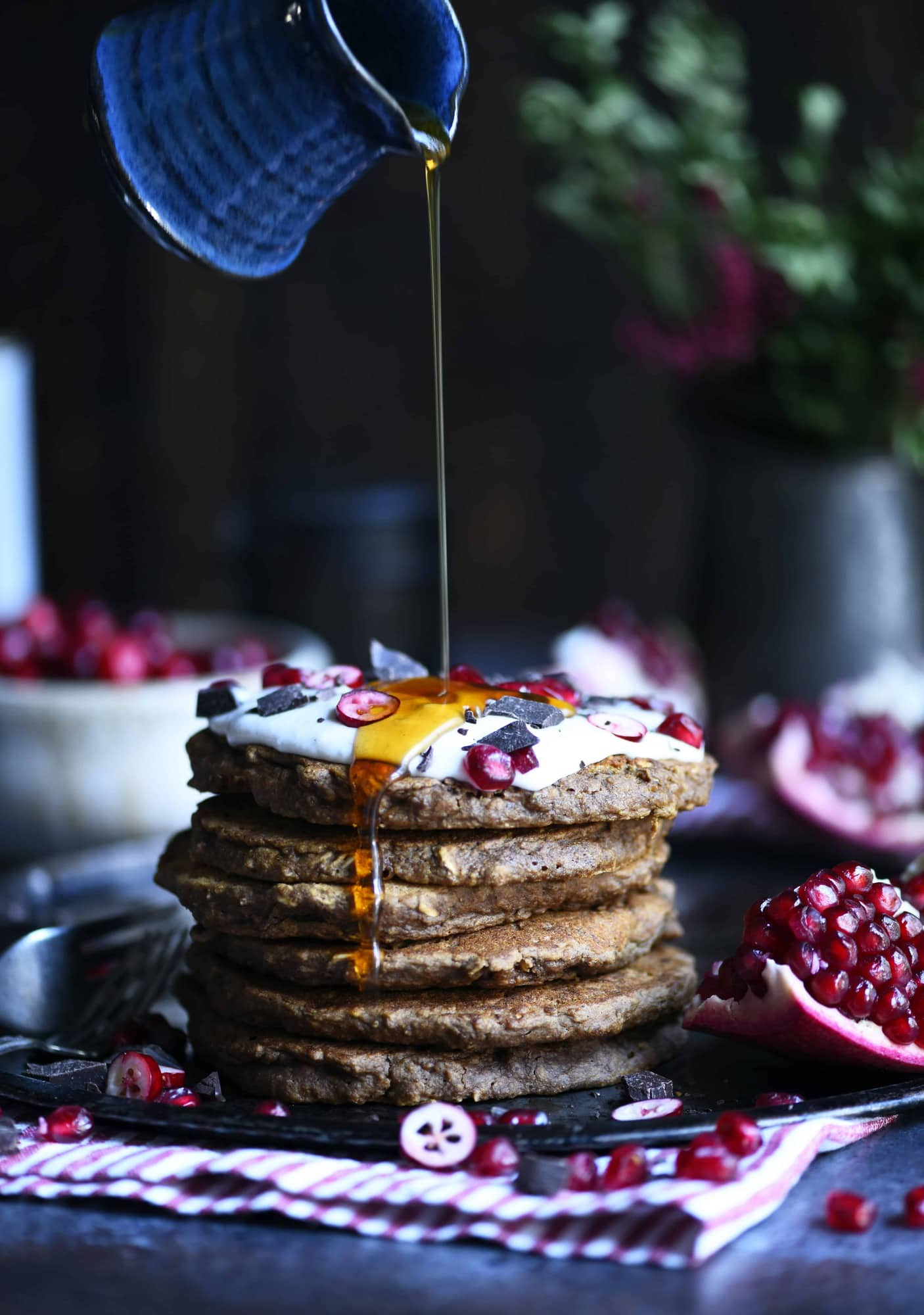 Pouring maple syrup onto a stack of gingerbread oatmeal pancakes with a dark background
