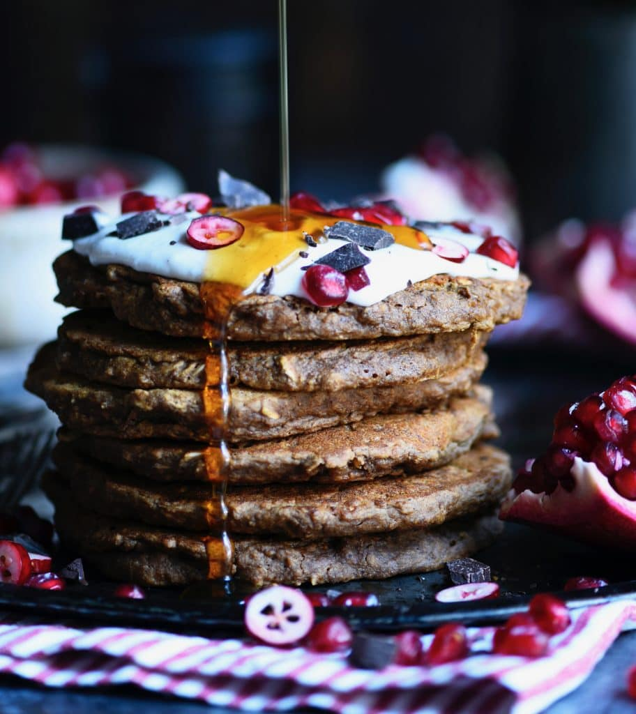 side view of gingerbread oatmeal pancakes in a stack with cream on top