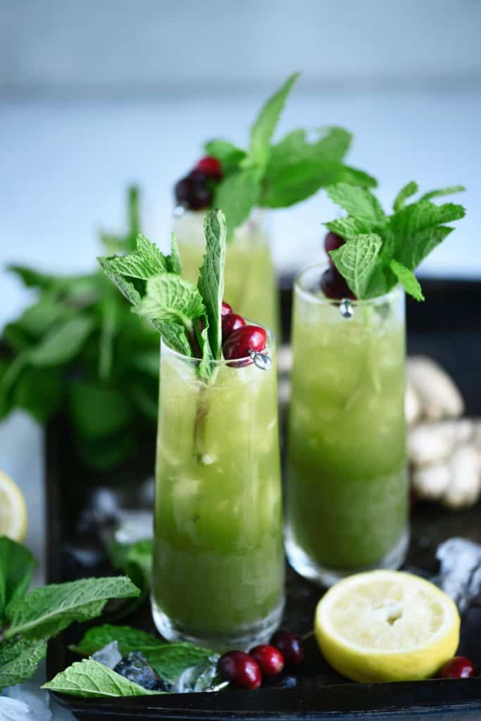 Side view of green matcha cocktail garnished with fresh mint