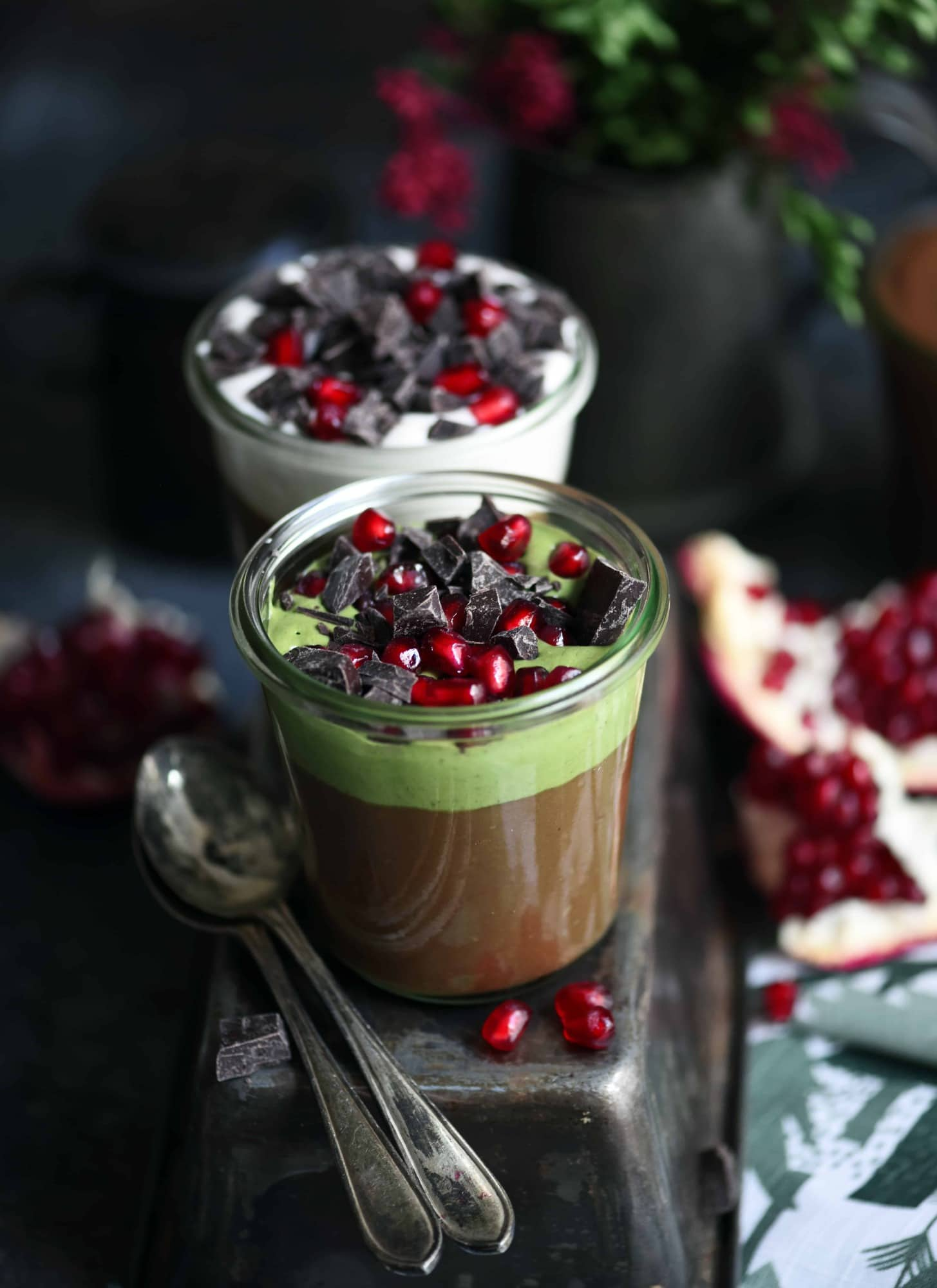 Jars filled with vegan chocolate and matcha mousse topped with chocolate and pomegranate on a dark background