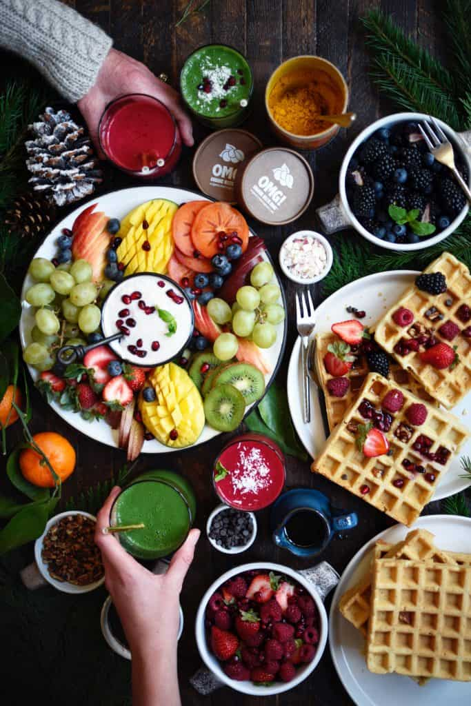 Overhead of spread with waffles and fruit on rustic wood background