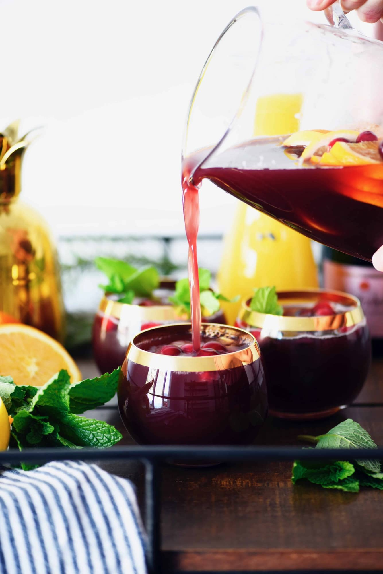 Pouring holiday sparkling punch into glasses on bar cart