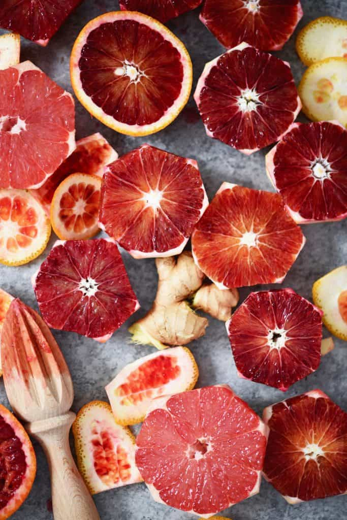 Overhead of sliced blood oranges, ginger and orange peels