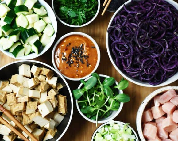 Overhead of stir fry prep with bowls of fresh vegetables, tofu and peanut sauce