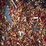Overhead of chocolate hazelnut raspberry granola on a sheet pan with a large spoon
