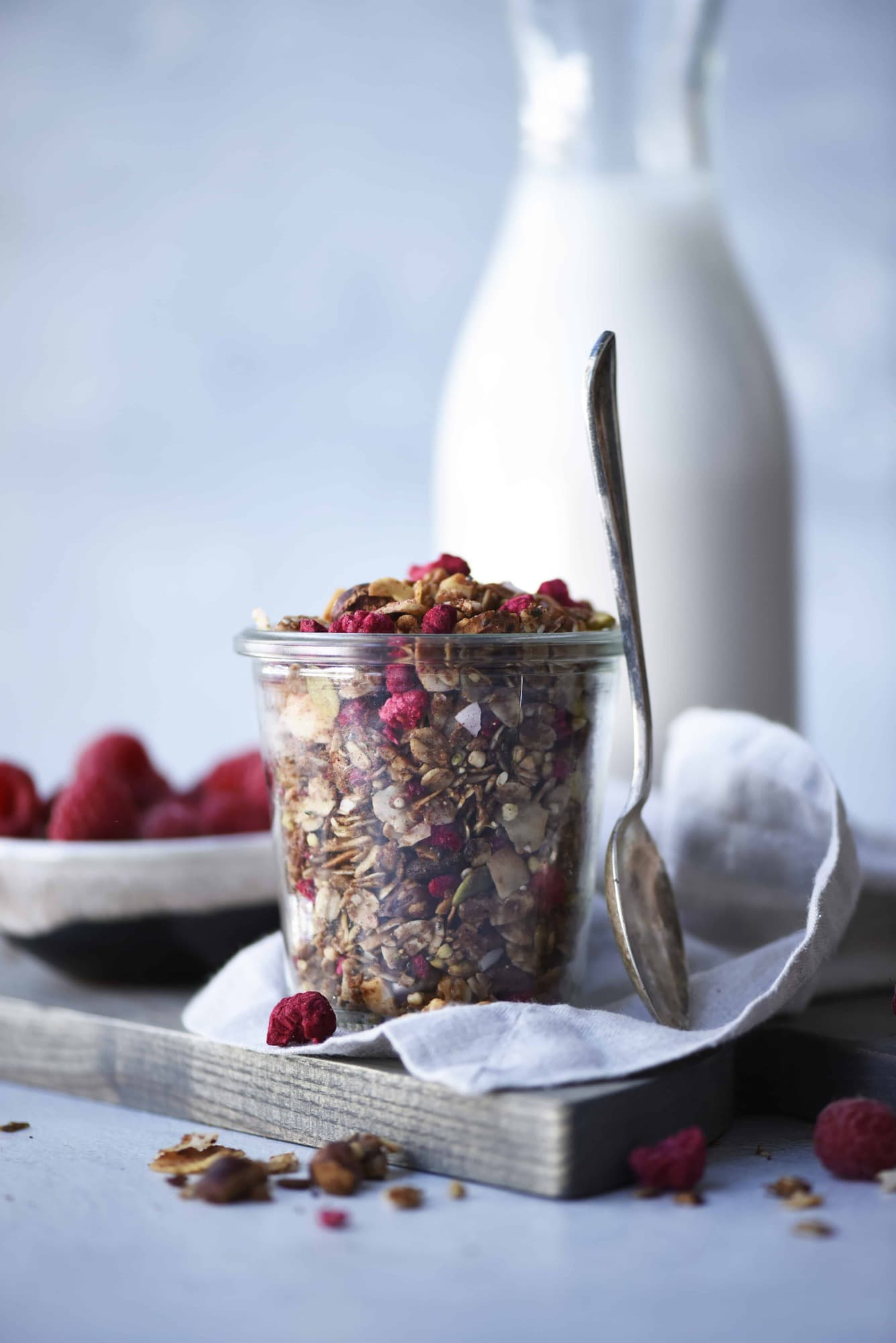 Side view of chocolate hazelnut raspberry granola in a glass jar with milk in the background