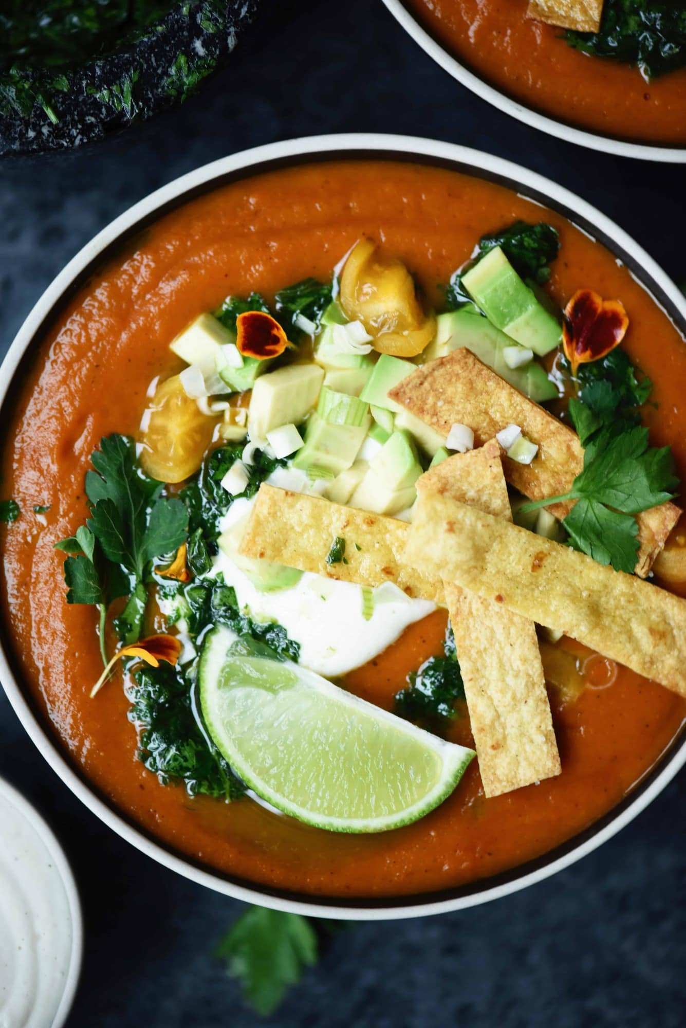 Overhead of fire roasted tomato soup with tortilla strips and avocado