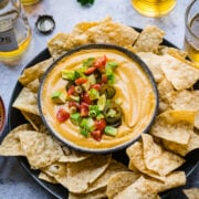 close up overhead view of vegan queso dip in a bowl with tortilla chips around it.