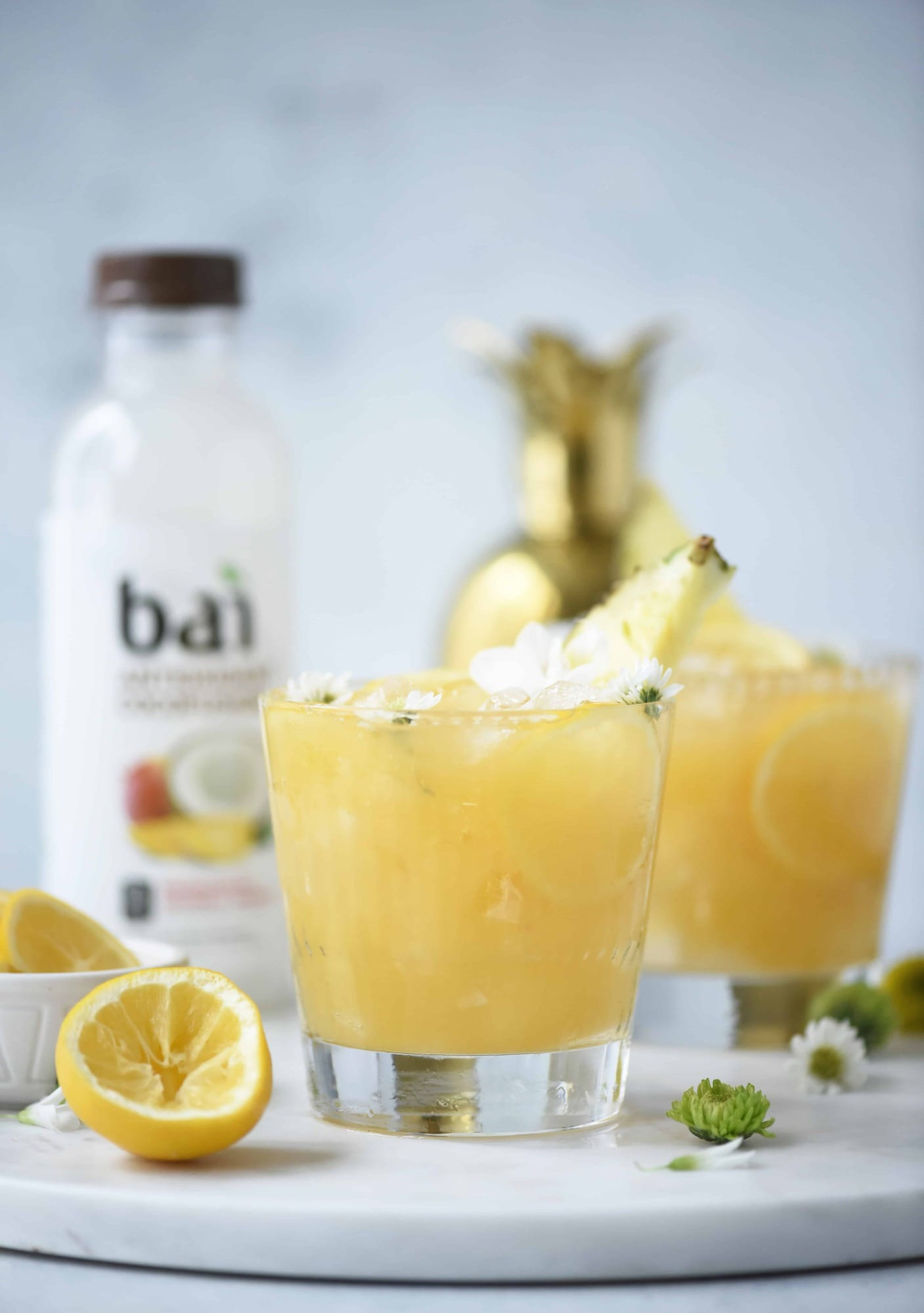 Side view of mango coconut pineapple rum punch on a white background