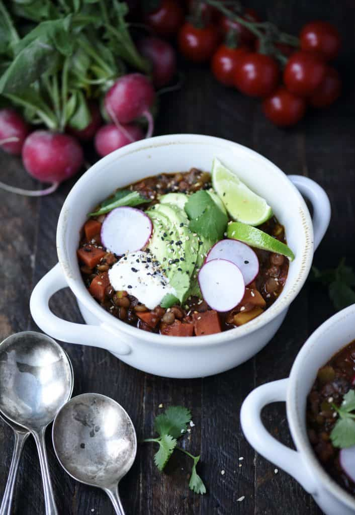 45 Degree Angle of vegan chili in a white pot with radishes and toppings