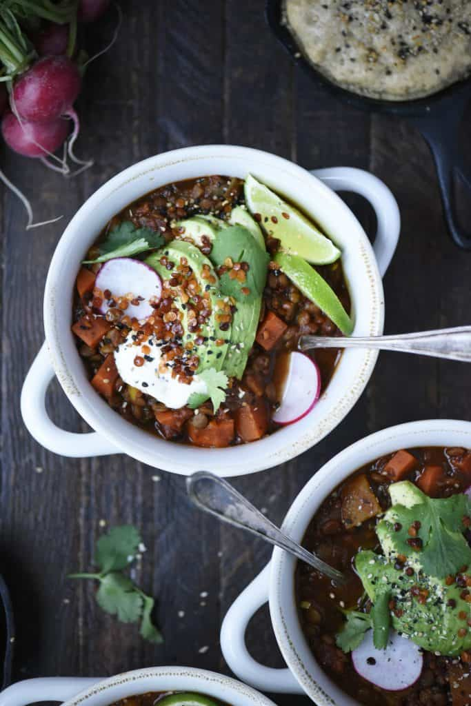 Overhead of vegan chili in a white bowl topped with avocado, lime, crispy lentils