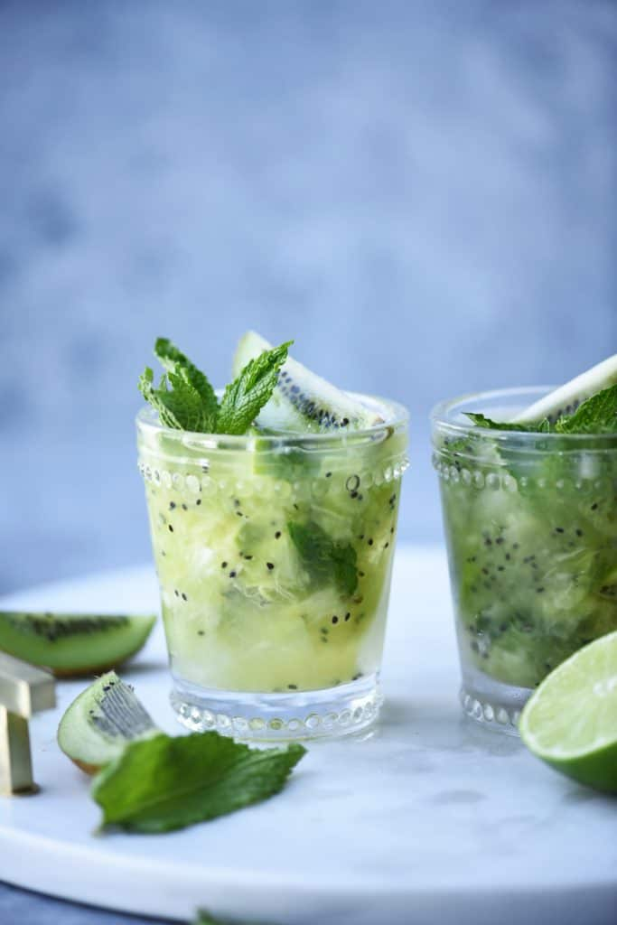 Side view of kiwi caipirinha garnished with fresh mint on a marble serving tray