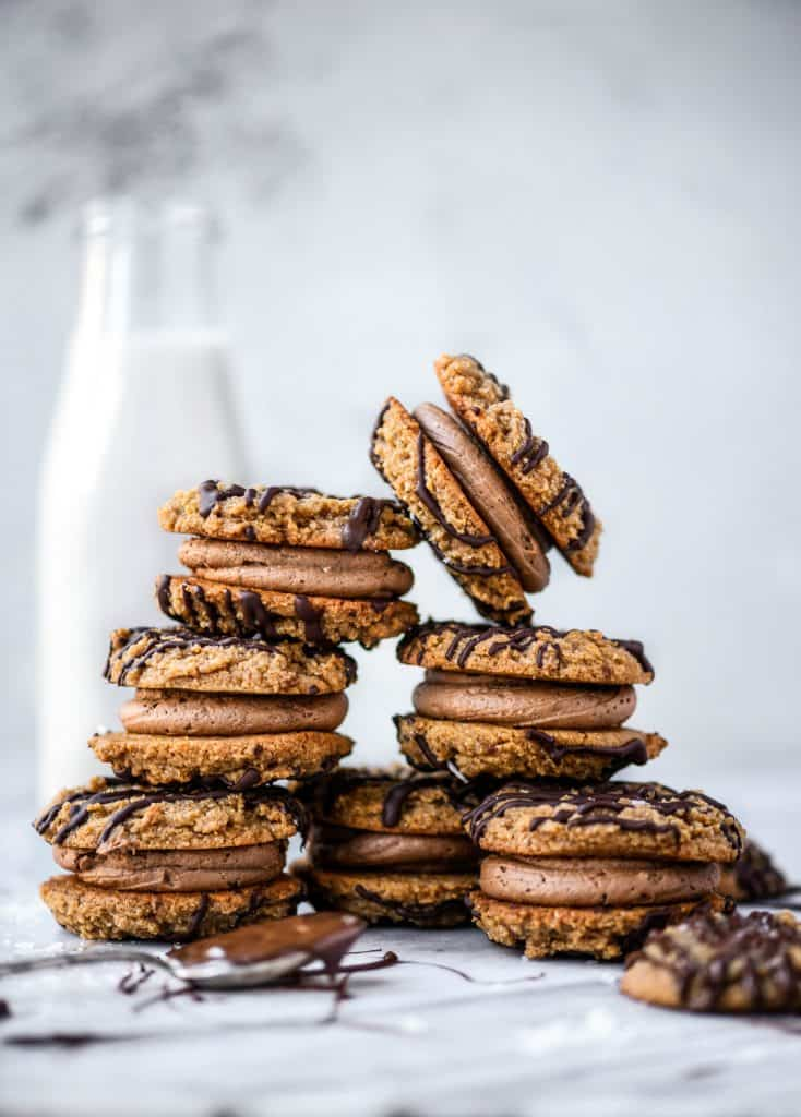Stack of peanut butter sandwich cookies drizzled with dark chocolate on a white marble background with jug of milk