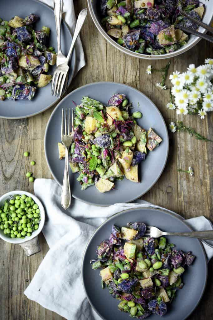 Overhead of purple potato spring salad in a white bowl with microgreens and fresh peas on a gray plate with an antique fork