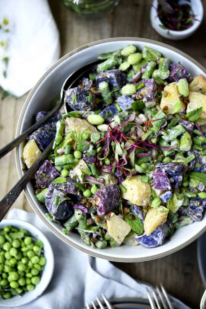 Overhead of purple potato spring salad in a white bowl with microgreens and fresh peas