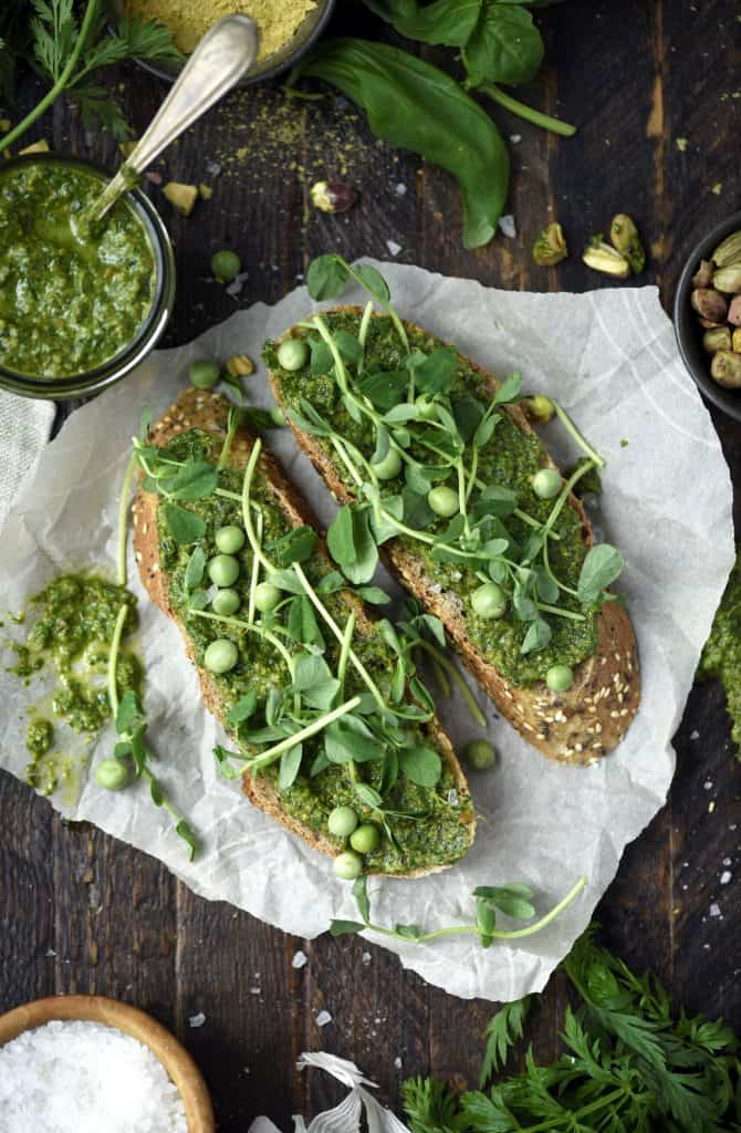 Overhead of two pieces of toast topped with vegan pesto, peas and greens