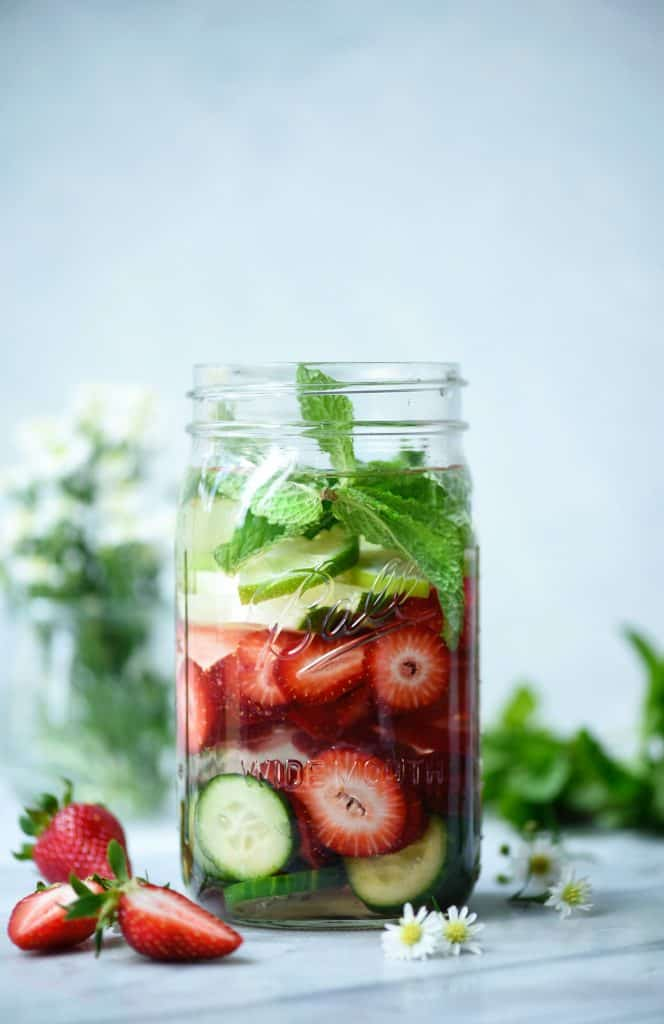 Large glass jar of strawberry cucumber mint infused water