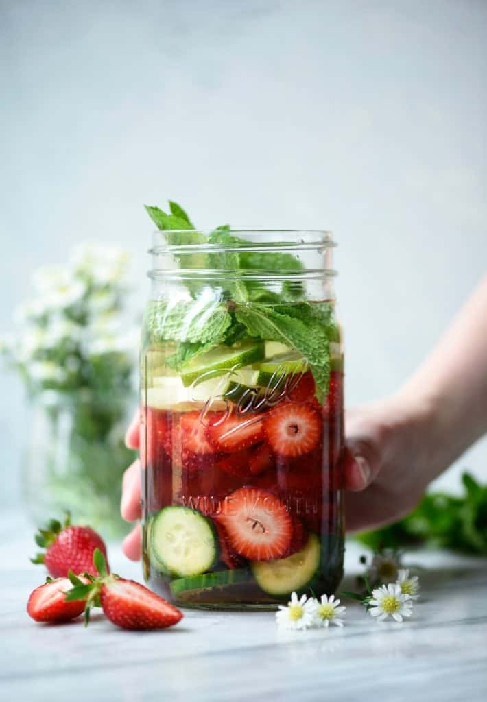 Hang grabbing large glass jar of strawberry cucumber mint infused water