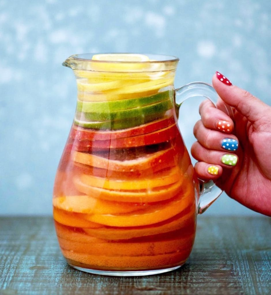 Rainbow citrus infused water with blue background