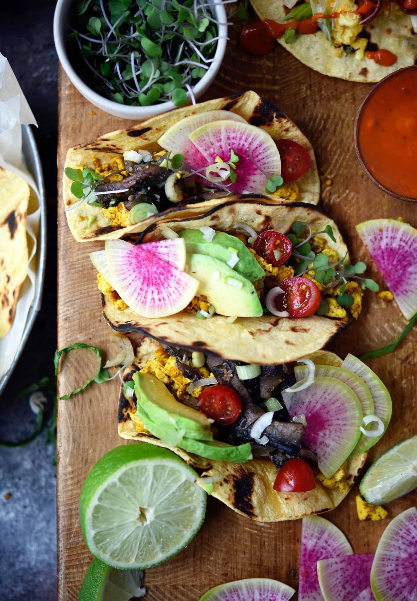 Close up of scrambled tofu breakfast tacos with watermelon radish and avocado