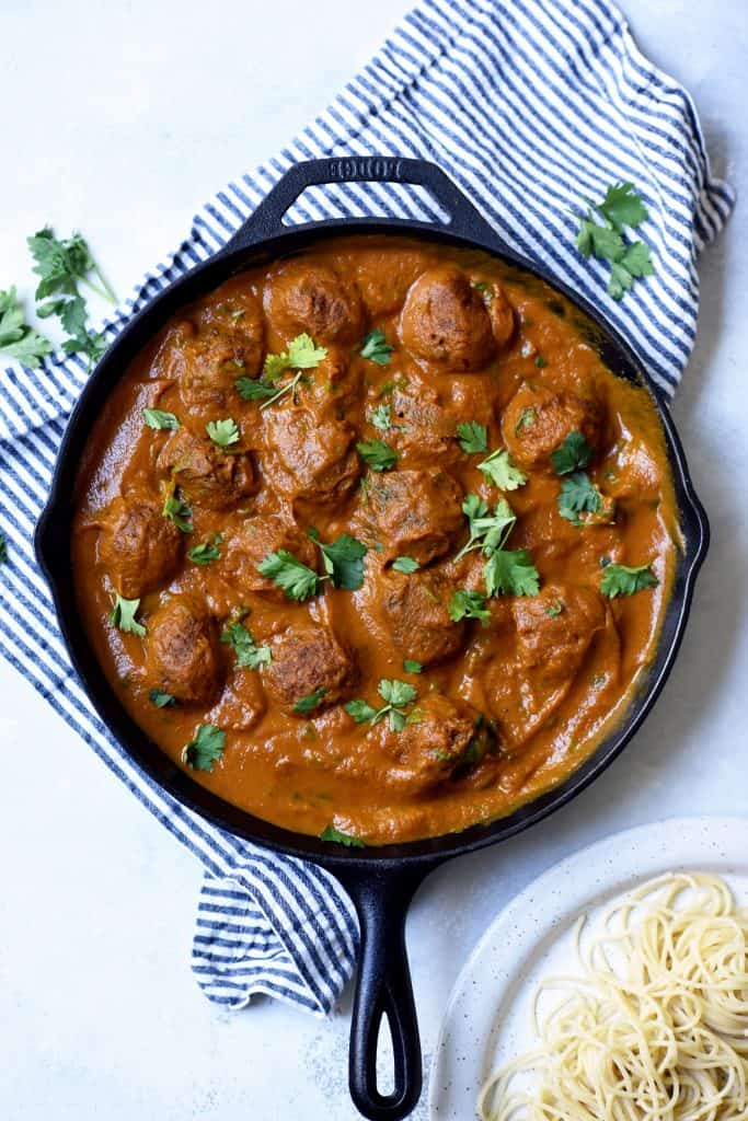 Overhead of vegan juice pulp meatballs in tomato sauce in a cast iron skillet