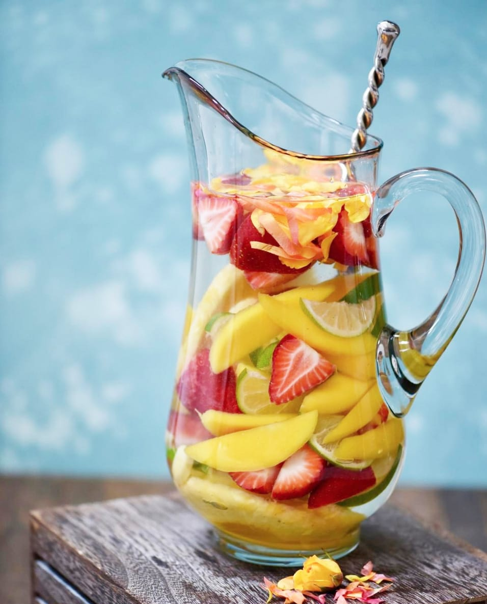 Large pitcher of mango, strawberry and lime infused water with blue background