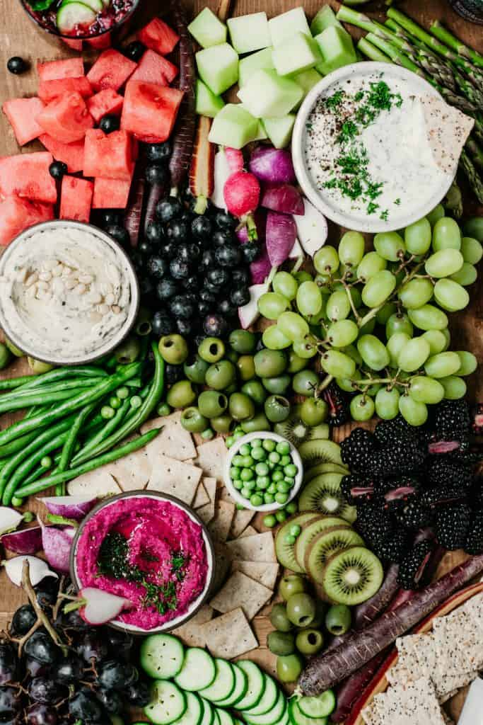 Close up of Overhead of snack platter on huge wood board with pink, purple and green vegetables
