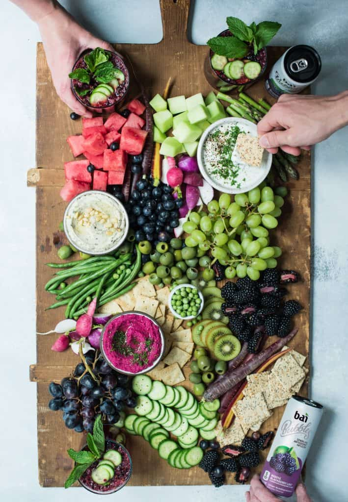Overhead of snack platter on huge wood board with pink, purple and green vegetables
