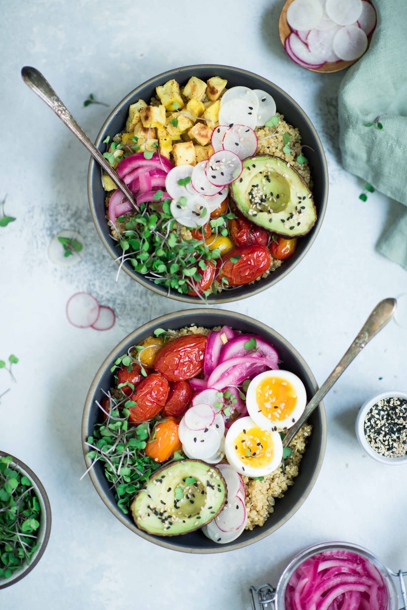 Overhead of two bowls of breakfast quinoa with avocado, radishes, scrambled tofu, soft-boiled eggs and microgreens