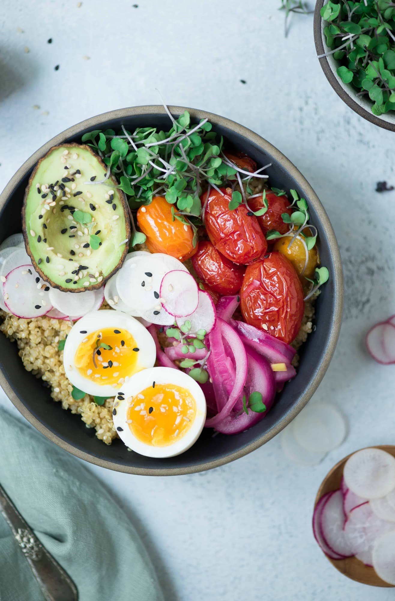 Close up Overhead of two bowls of breakfast quinoa with avocado, radishes, scrambled tofu, soft-boiled eggs and microgreens