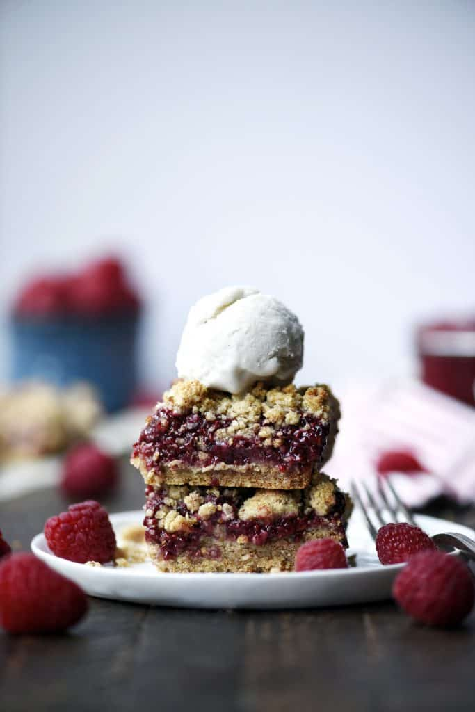 Stacked gluten free raspberry oatmeal crumble bars with a scoop of vanilla ice cream and fresh raspberries on a small white plate