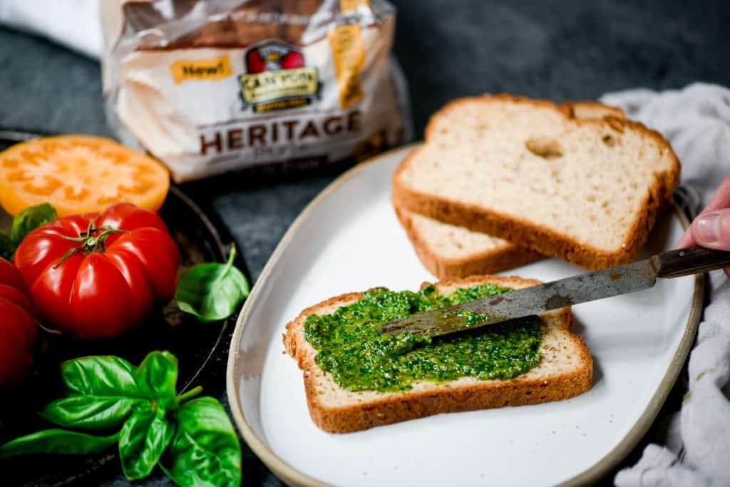 Spreading pesto onto gluten free bread on a white plate