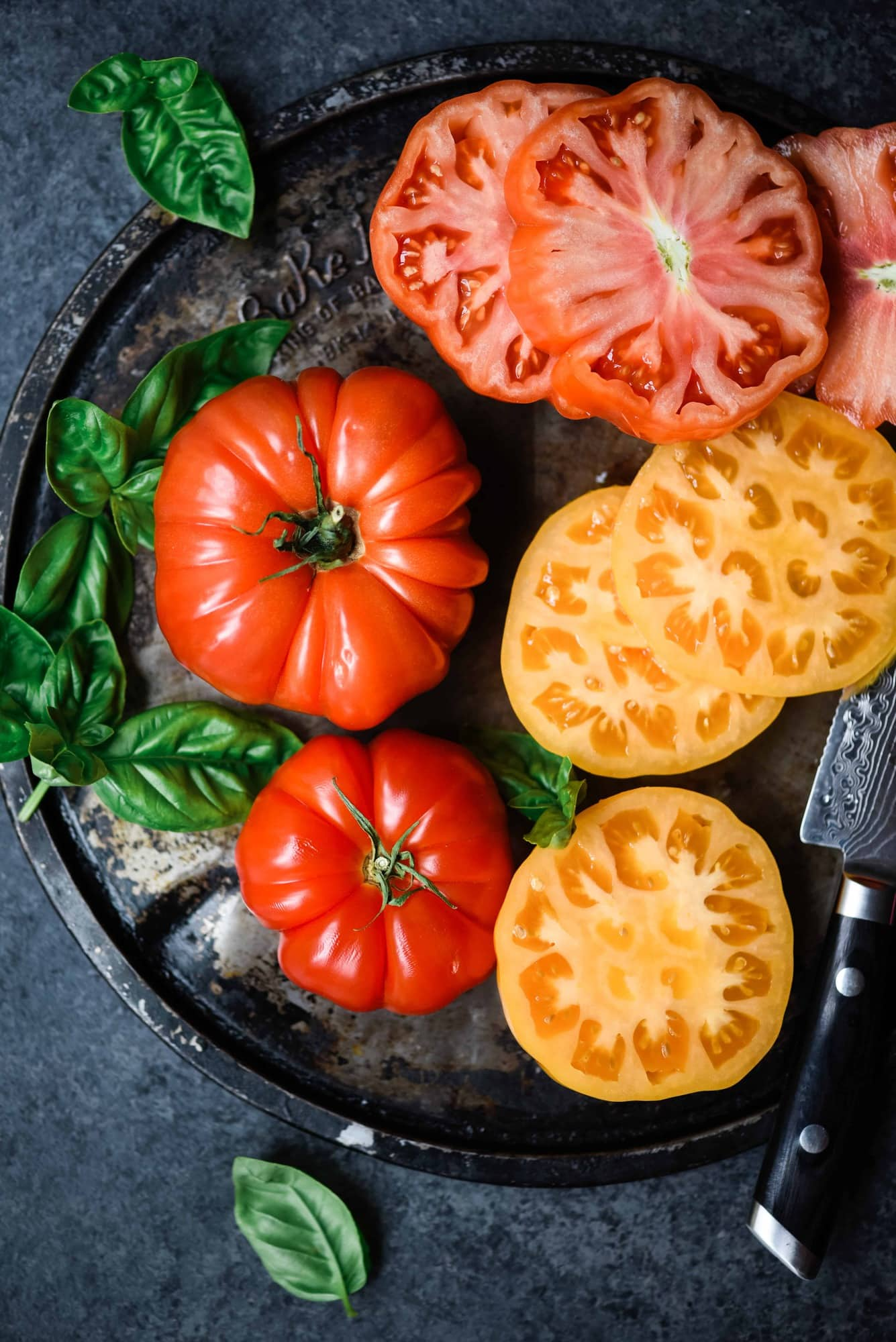 Overhead of beautiful red and yellow heirloom tomatoes with fresh basil