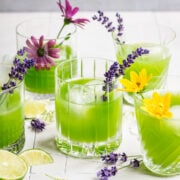 Green cocktail in cocktail glasses garnished with flowers.