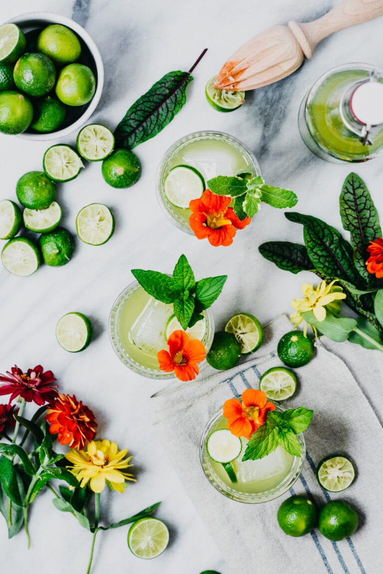 Overhead of green cocktail with key limes and flowers
