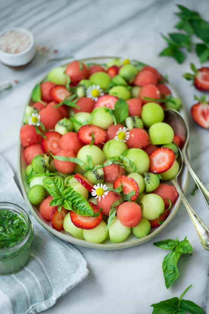 Side view of melon ball salad on a white platter with strawberries and a lime mint dressing on a white marble backdrop