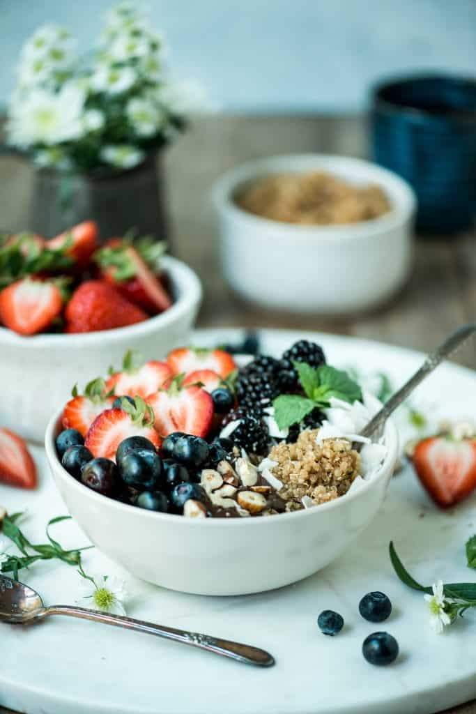 Side view of breakfast quinoa in a white bowl with fresh berries, coconut and hazelnuts on a white marble serving tray