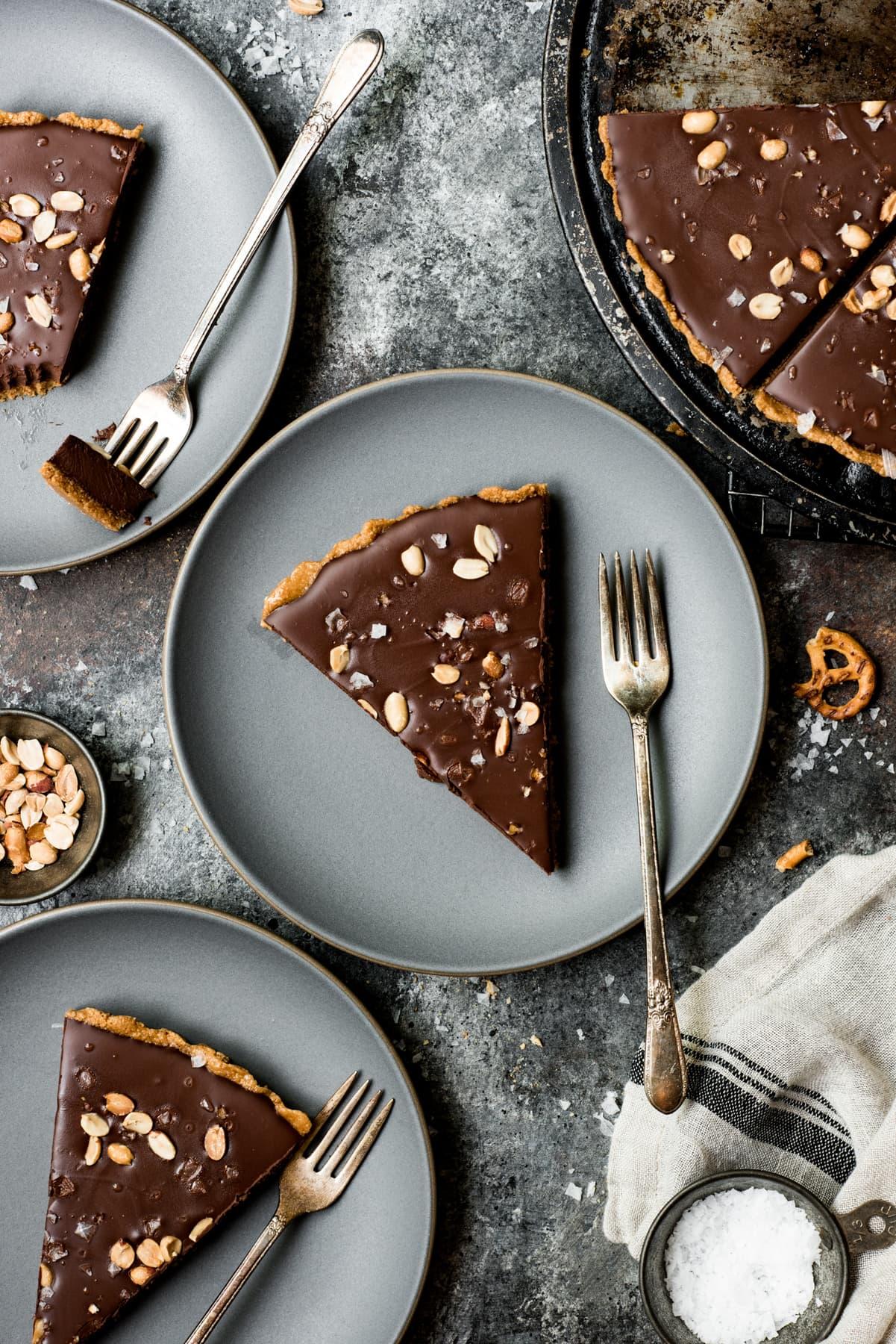 overhead view of vegan peanut butter chocolate pretzel tart on plates