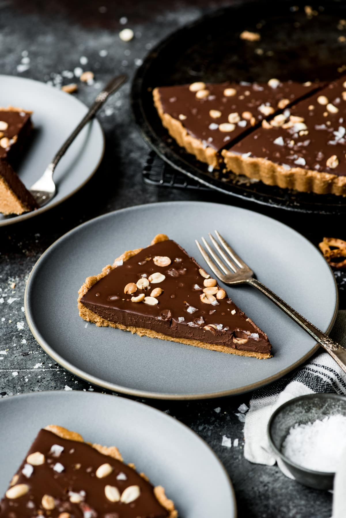 side view of slice of chocolate peanut butter pretzel tart on a plate