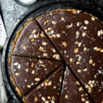 Overhead of chocolate ganache pretzel tart on a cooling rack with dark, moody background