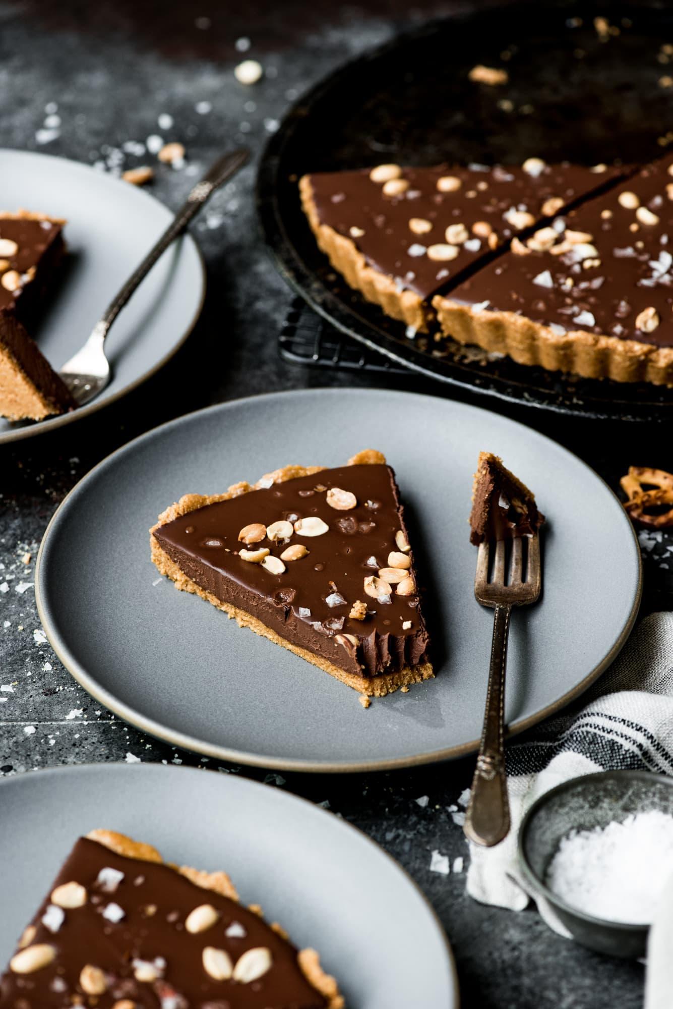 Peanut butter pretzel chocolate tart on a dark plate with fork