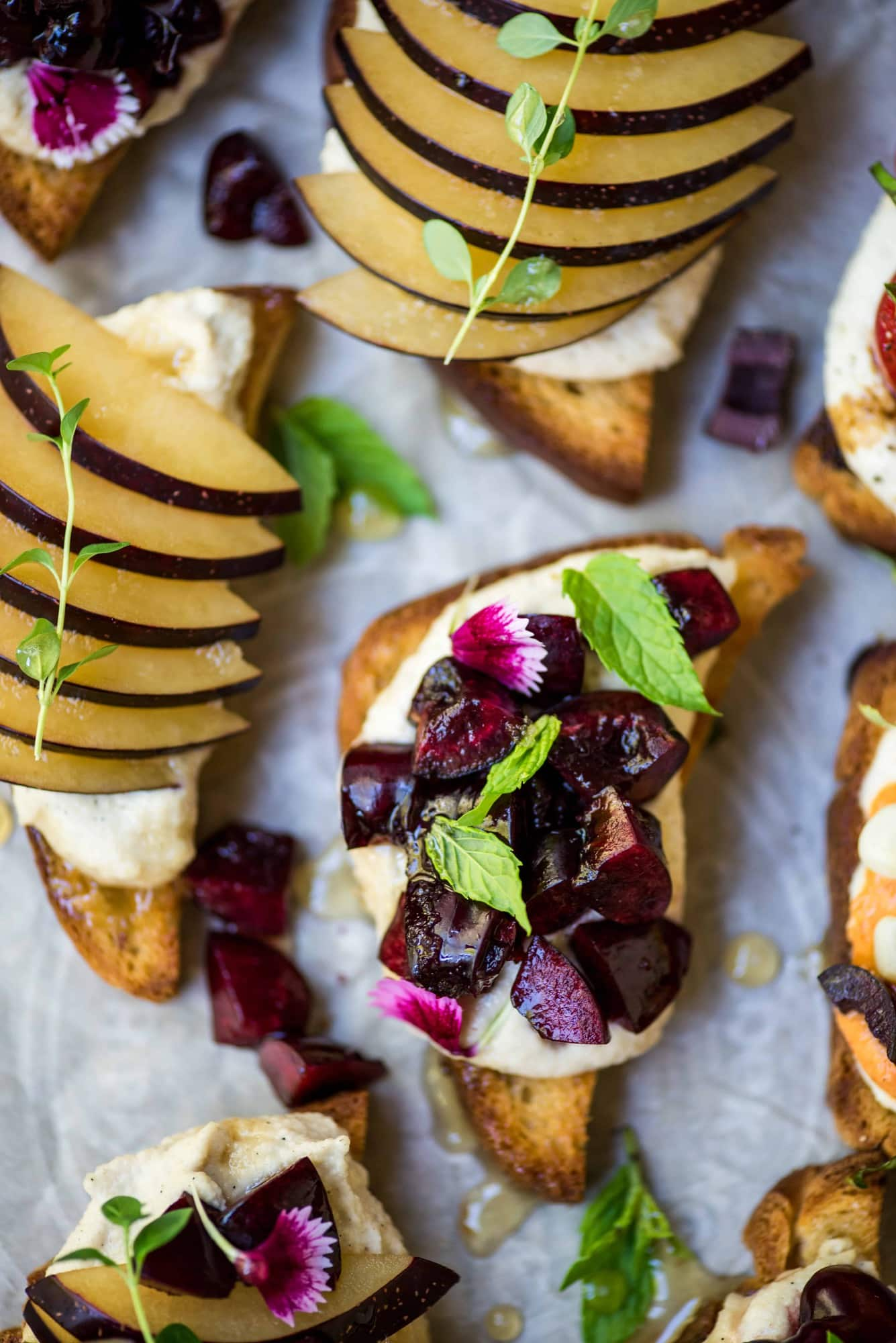 Close up of crostini topped with cherries, plum, ricotta and herbs