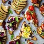 Overhead of crostini topped with ricotta, herbs, tomatoes, cherries and plums