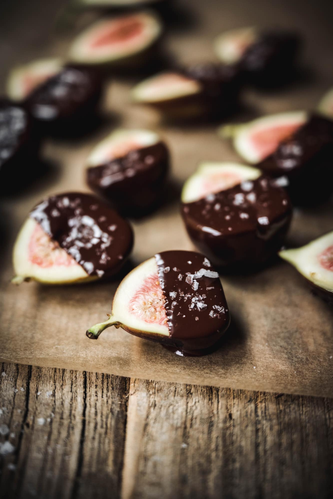 Side view of chocolate dipped figs with flaky sea salt
